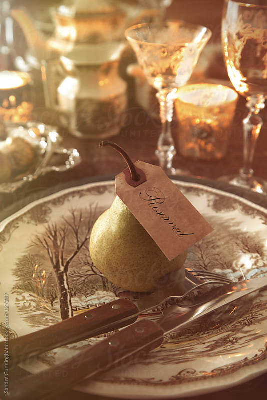 Festive place tag with pear on place setting for the holidays by Sandra Cunningham for Stocksy United