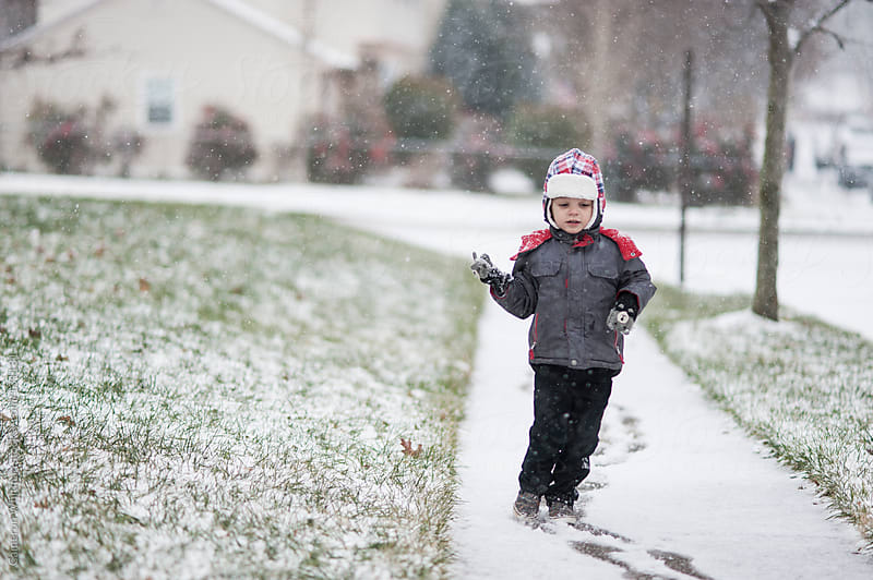 Young boy sliding on the sidewalk during first snowfall by Cameron Whitman for Stocksy United