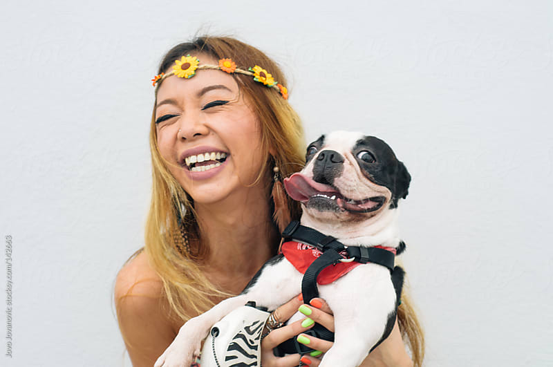 Blond Asian woman holding her happy, smiling dog. by Jovo Jovanovic for Stocksy United