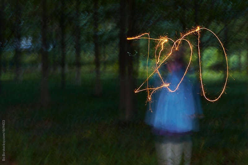 woman painting I Love you with sparkler in the woods by Bo Bo for Stocksy United