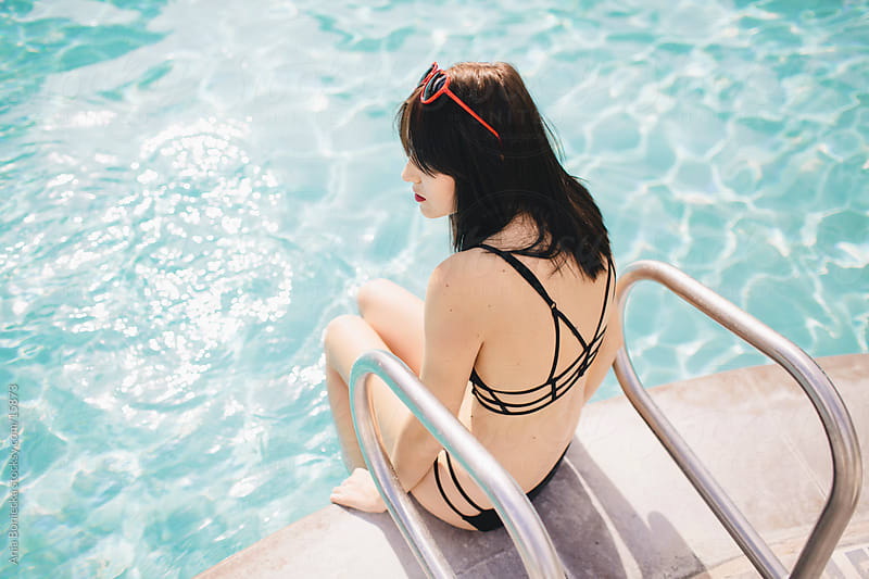 A woman sitting at the edge of the pool ready to jump in by Ania Boniecka for Stocksy United