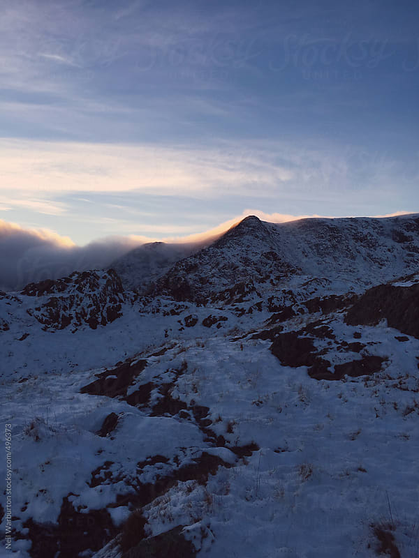 Sunset over winter mountains by Neil Warburton for Stocksy United