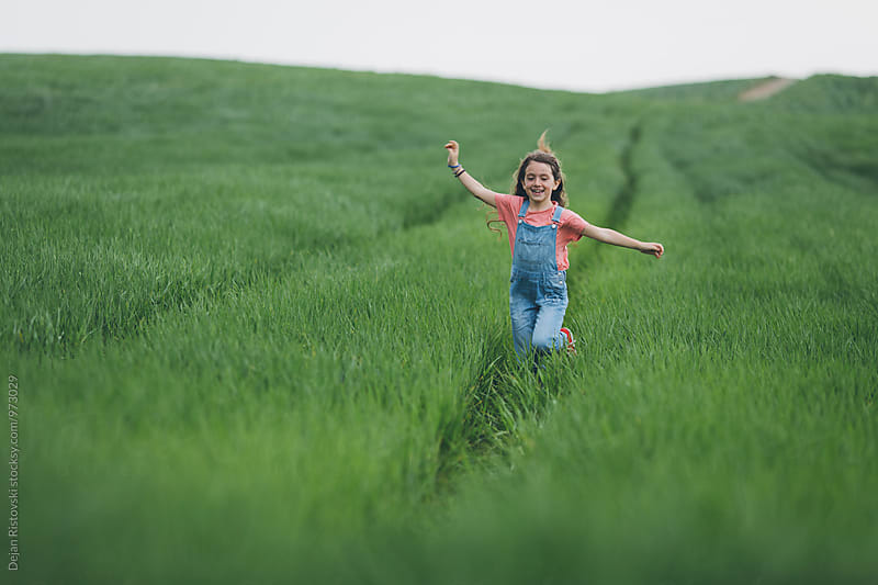Happy little girl running along green wreath field. by Dejan Ristovski for Stocksy United