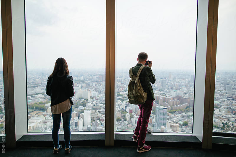 Back view of tourist friends taking photos of Tokyo skyscraper.  by BONNINSTUDIO for Stocksy United