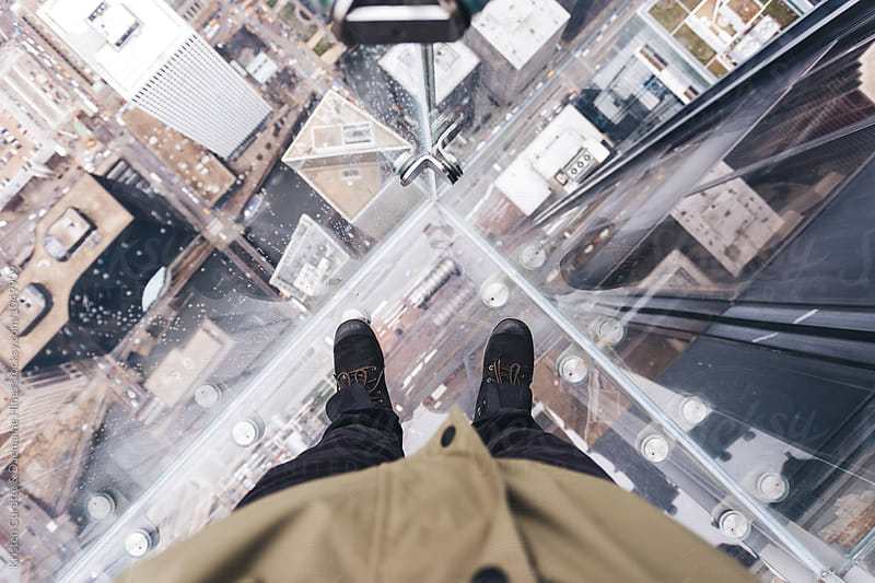 First person view of someone looking down through a glass deck up high  by Kristen Curette Hines for Stocksy United