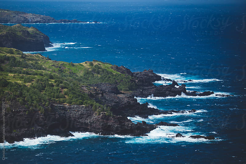 View down on rocky coastline with waves crashing by Christian Tisdale for Stocksy United