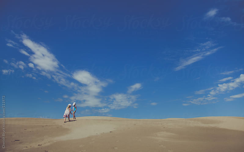 Two little girls running through the sand dunes with the big blue sky on the horizon. by Cherish Bryck for Stocksy United