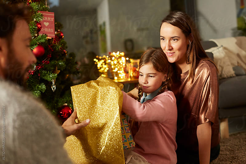 Happy Family Opening Christmas Present At Home by ALTO IMAGES for Stocksy United