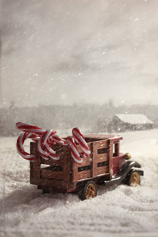 Small toy truck with candy canes in snow by Sandra Cunningham for Stocksy United