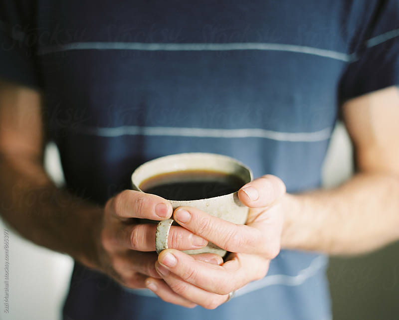 Man holding a cup of black coffee by Suzi Marshall for Stocksy United