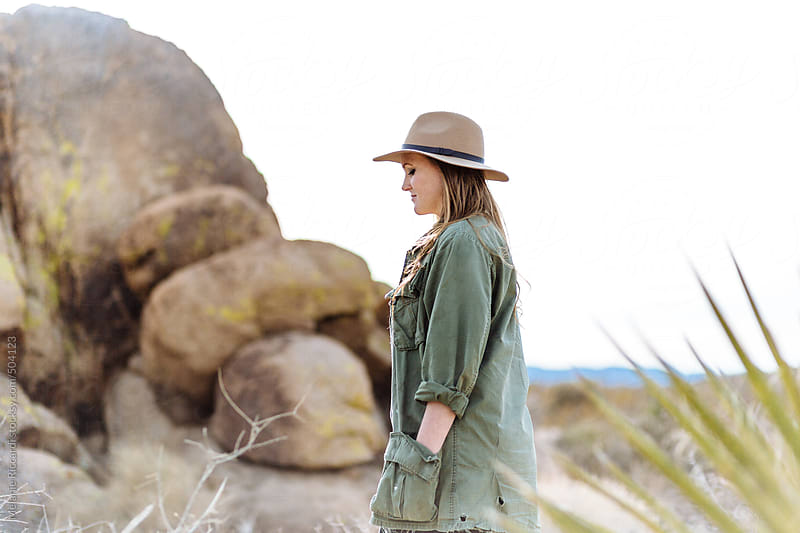 Woman walking in desert wearing a hat by Melanie Riccardi for Stocksy United