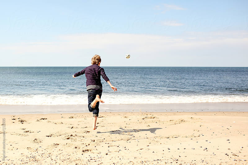 Boy performing a soccertrick on the beach by Marcel for Stocksy United