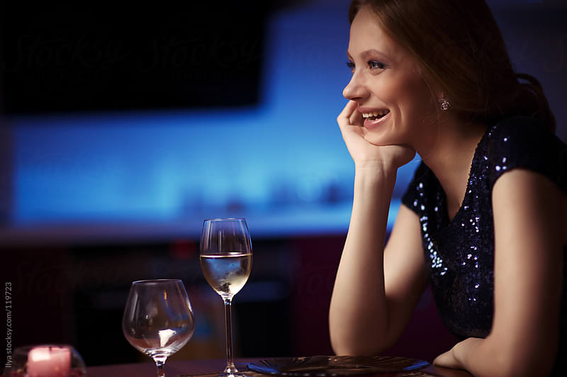 Young happy woman in restaurant by Ilya for Stocksy United