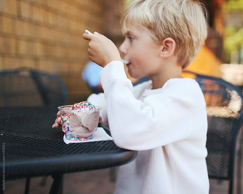 boy eating ice cream by Kelly Knox for Stocksy United