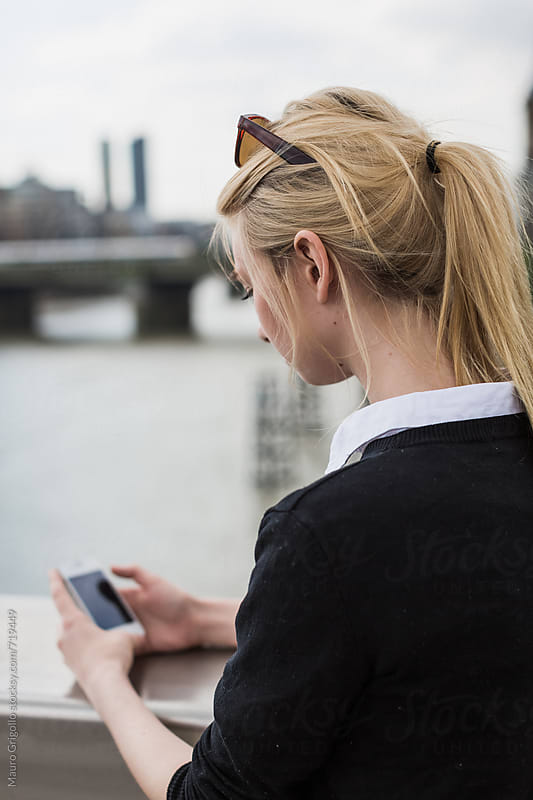 Business woman using a smartphone outdoor by Mauro Grigollo for Stocksy United
