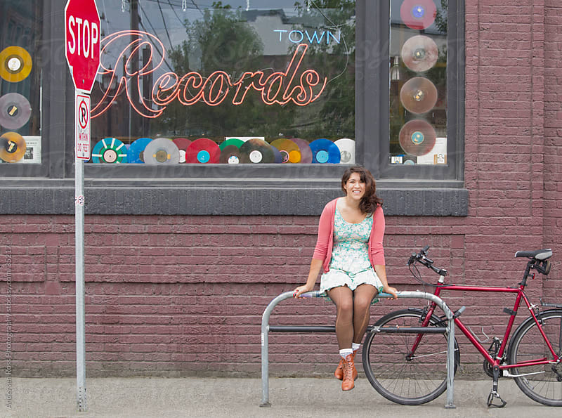 Young woman sitting on railing in front of record shop by Andersen Ross Photography for Stocksy United