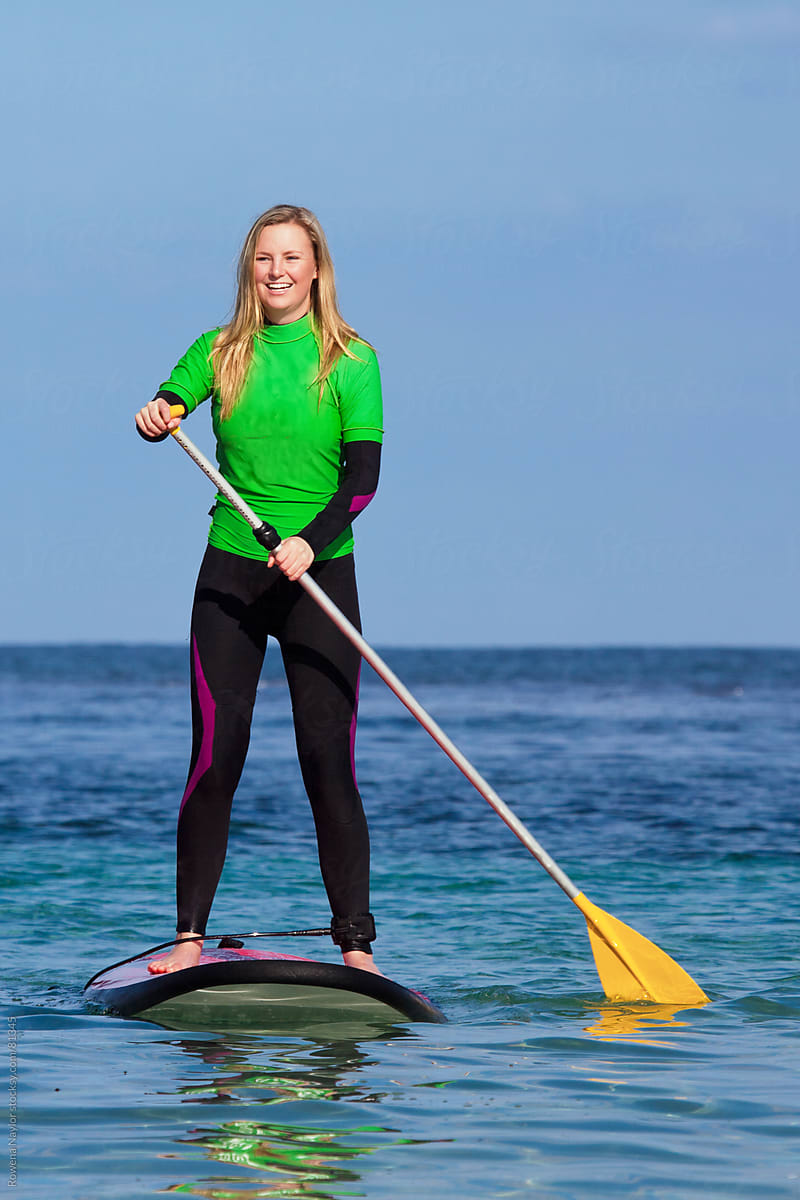 4cf2b984702 Young woman on Stand Up Paddle Board on the ocean by Rowena Naylor for  Stocksy United