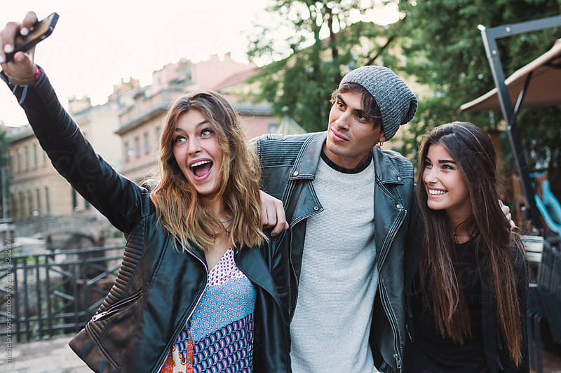 Smiling friends taking a selfie together by michela ravasio for Stocksy United