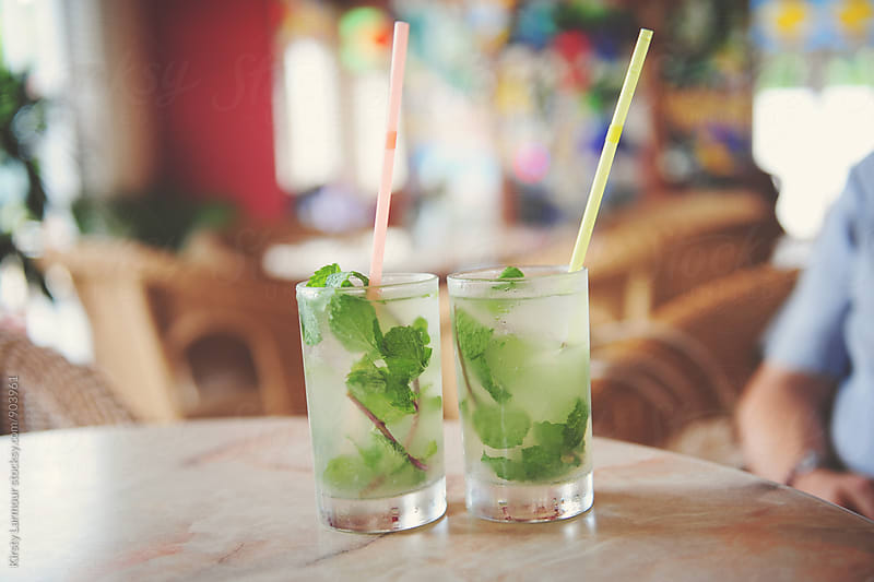 2 mojitos sitting on a table in a bar in Cuba by Kirsty Larmour for Stocksy United