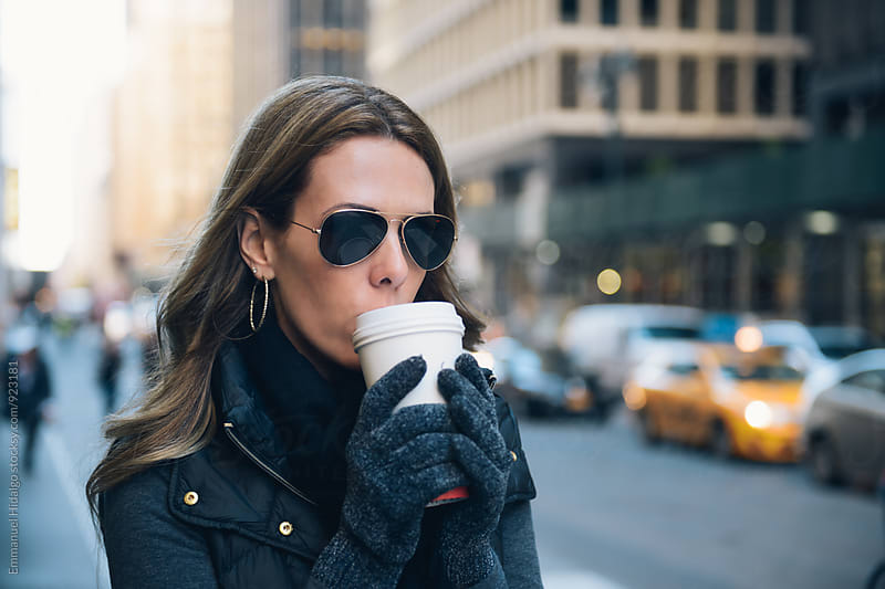 Woman having her morning coffee in the city streets by Emmanuel Hidalgo for Stocksy United
