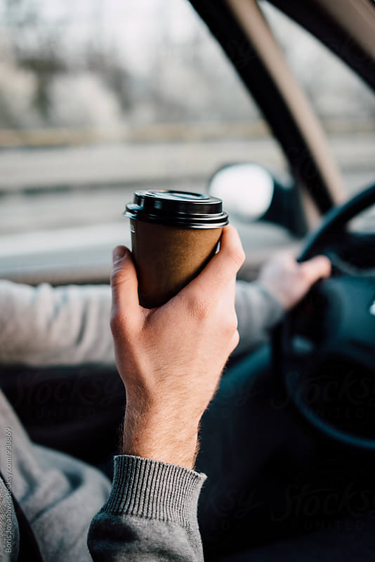 Man driving a car and holding a cup of coffee by Boris Jovanovic for Stocksy United