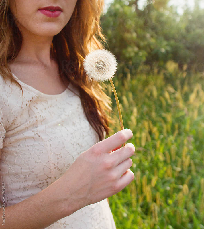 young woman holding dandelion by Tana Teel for Stocksy United