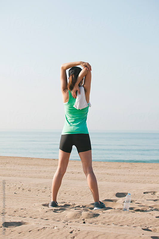 Sport girl doing stretching exercises after run workout on the beach. by BONNINSTUDIO for Stocksy United