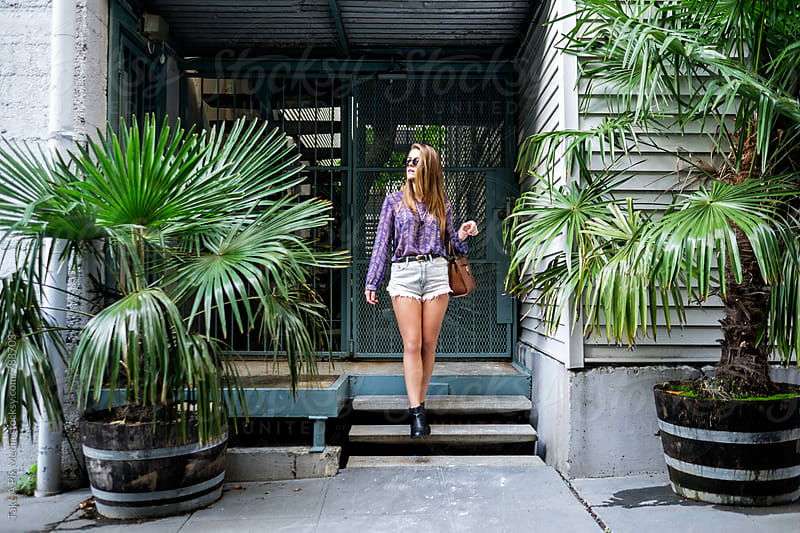 Beautiful young woman coming out of a building by Suprijono Suharjoto for Stocksy United