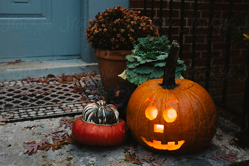 Lit Jack-O-Lantern on the front stoop by Cameron Whitman for Stocksy United