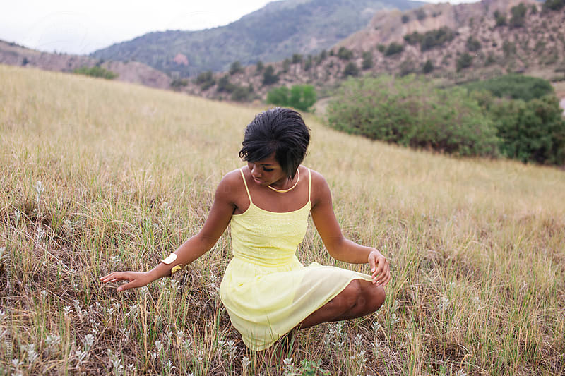 Black girl in yellow dress sitting down in a field by Gabrielle Lutze for Stocksy United