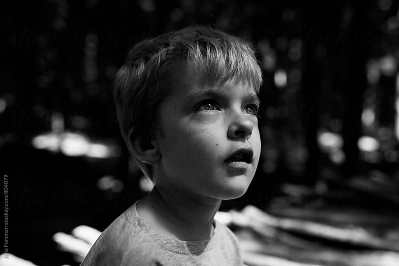 Boy in black and white with beautiful light falling on his face by Julia Forsman for Stocksy United