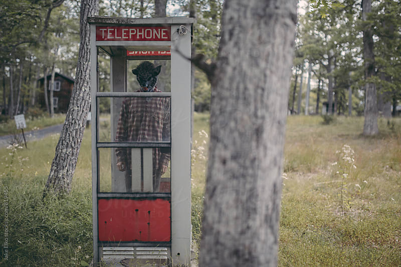 Creepy Abandoned Resort Man With Mask in Phone Booth by Jake Elko for Stocksy United