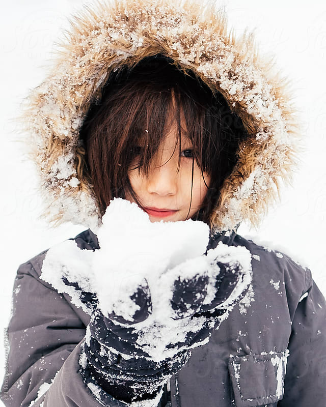 Young mixed race boy holds handful of snow by kelli kim for Stocksy United