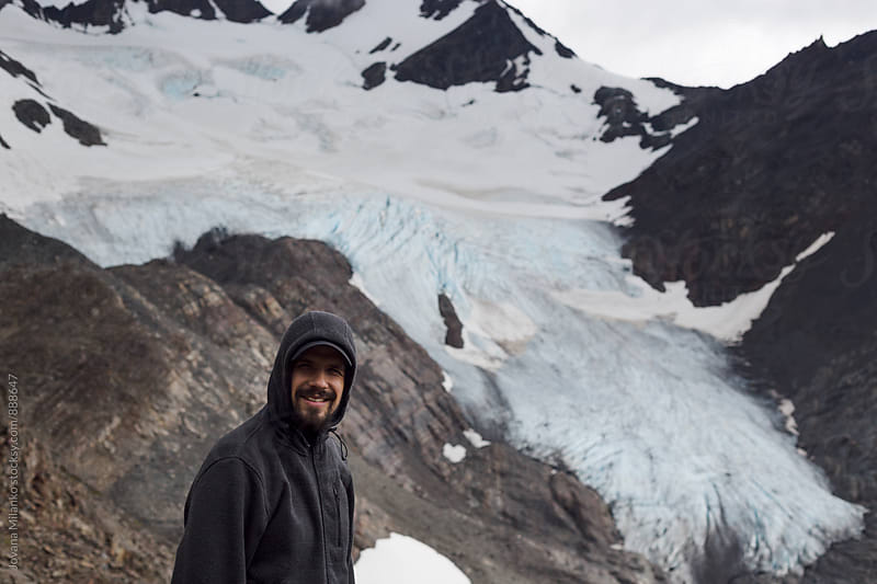 Portrait of a man standing in front of a glacier by Jovana Milanko for Stocksy United