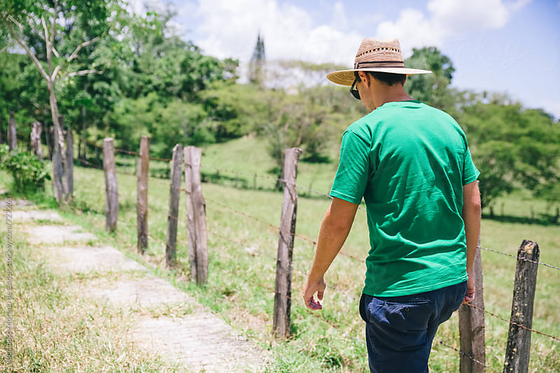 Young man with straw hat walking on a countryside path by Alejandro Moreno de Carlos for Stocksy United
