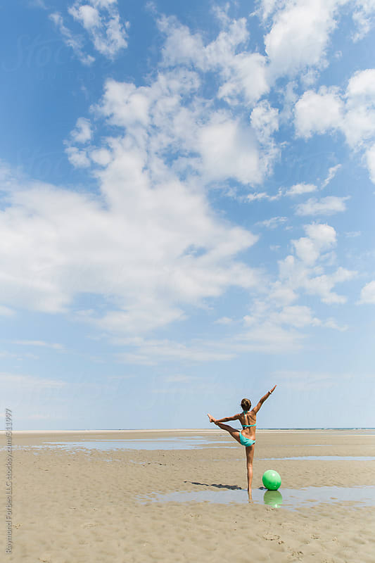 Young Girl doing Yoga on the Beach by Raymond Forbes LLC for Stocksy United