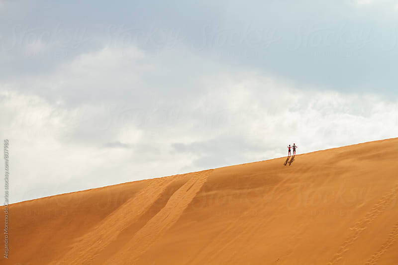 Two adventurous people at the top of a sand dune in the desert by Alejandro Moreno de Carlos for Stocksy United