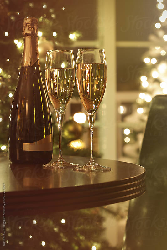 Glasses of champagne and bottle with festive background by Sandra Cunningham for Stocksy United