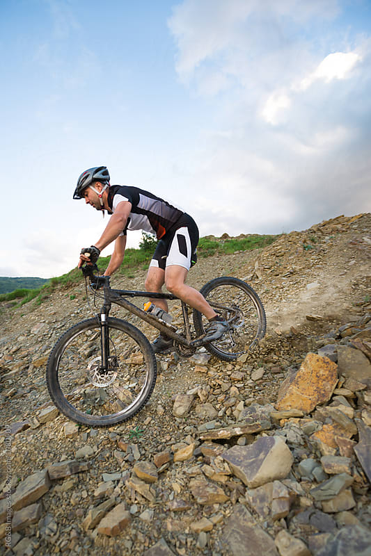 Man riding a mountain bike in downhill style by RG&B Images for Stocksy United