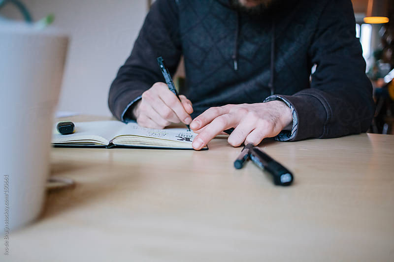 Close up of a designer working at his desk at home by Ivo de Bruijn for Stocksy United