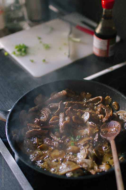 Cooking mushrooms in a pan by Davide Illini for Stocksy United