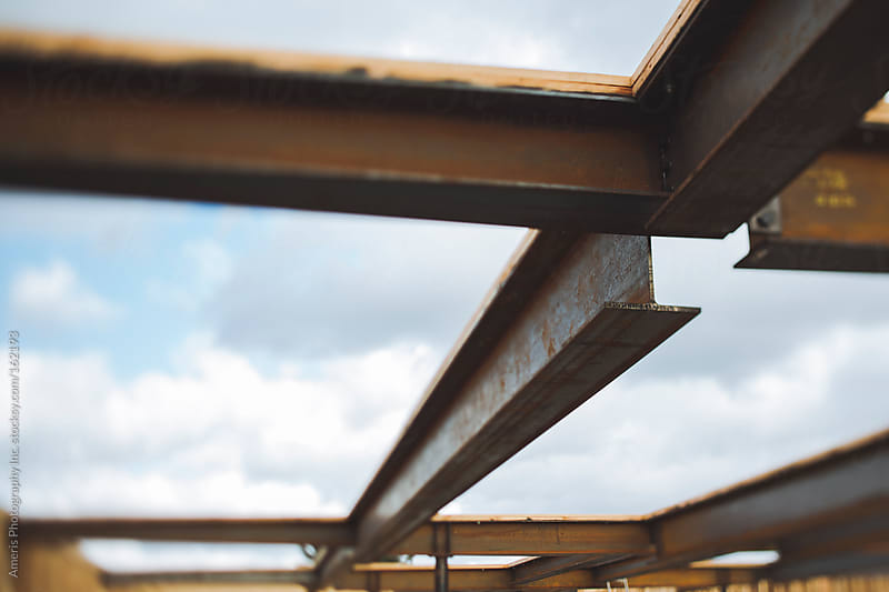 Steel beams and sky at construction site by Rob and Julia Campbell for Stocksy United