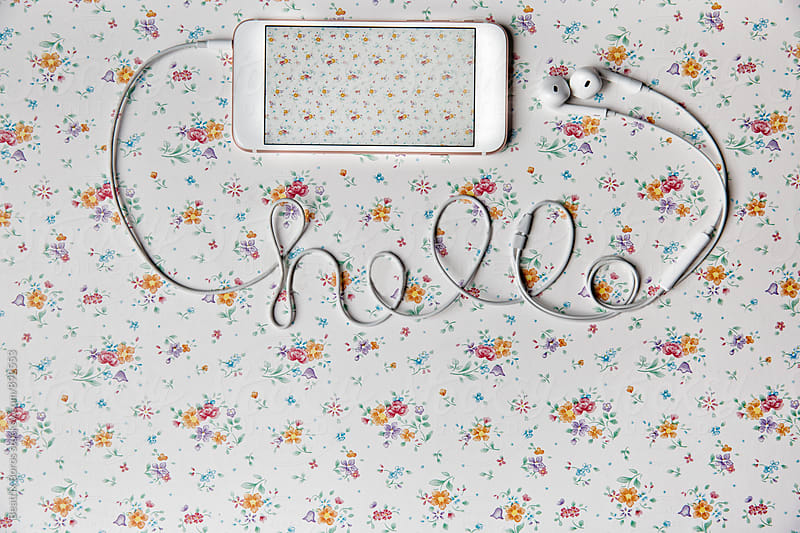 Mobile phone on a floral pattern with hello written with cable by Beatrix Boros for Stocksy United