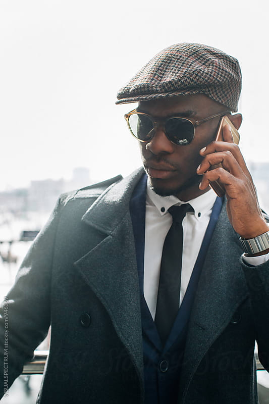 Portrait of Well-Dressed Young Black Businessman Making Phone Call by VISUALSPECTRUM for Stocksy United
