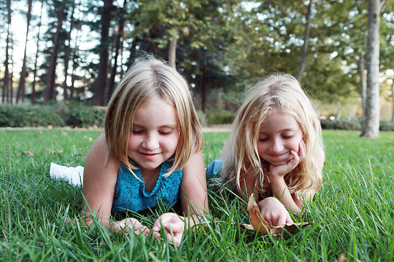 Young Blonde Sisters Laying On Grass by Dina Giangregorio for Stocksy United