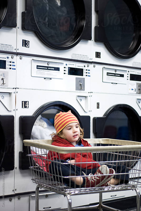 Boy rests in laundry cart at laundromat by Cara Dolan for Stocksy United