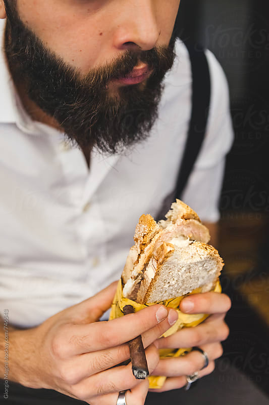 Young Bearded Man Eating a Rustic Sandwich Panino in Italy by Giorgio Magini for Stocksy United
