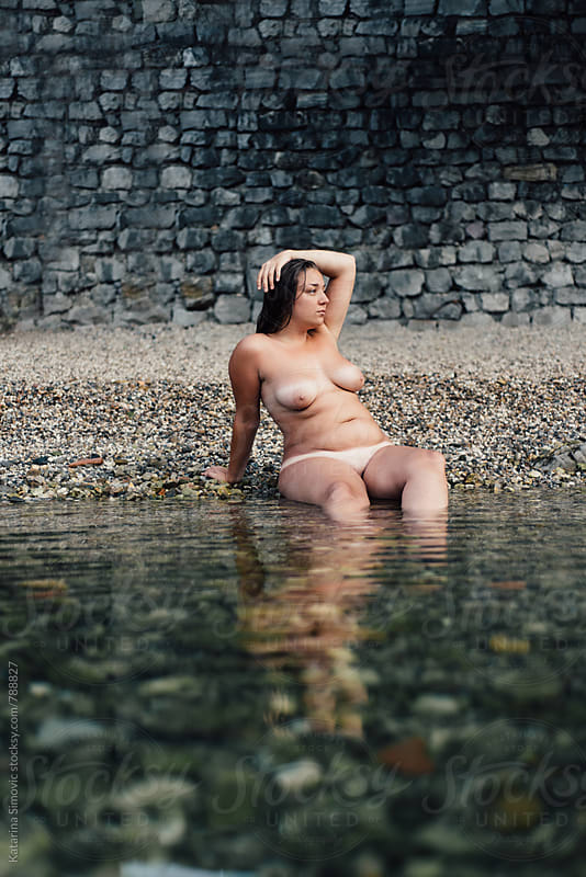Young naked woman sitting on beach by Katarina Simovic for Stocksy United