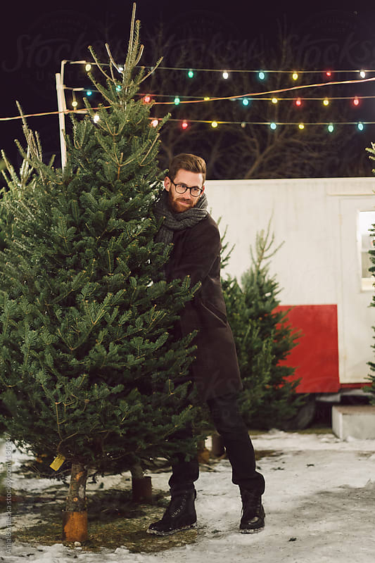 A man lifting a christmas tree by Ania Boniecka for Stocksy United