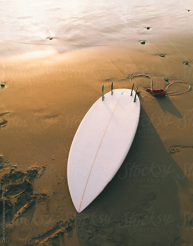 Surfboard washed up onto the a beach. by Denni Van Huis for Stocksy United